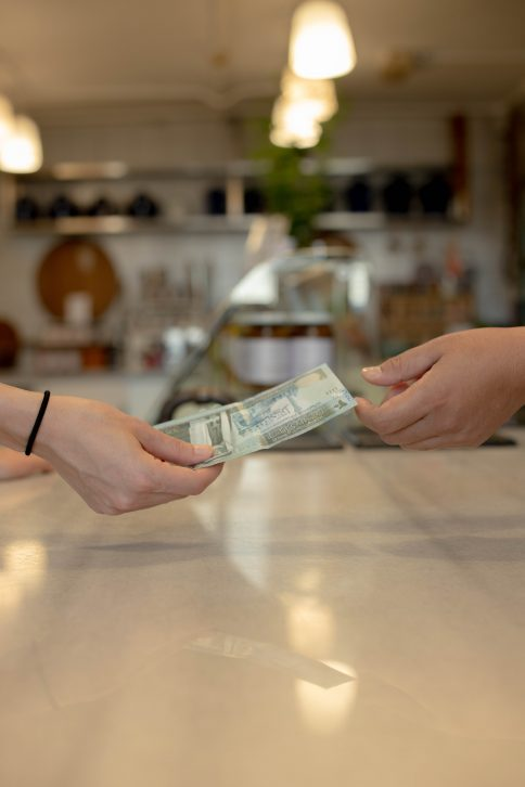 Two hand exchanging twenty jordanian dinars